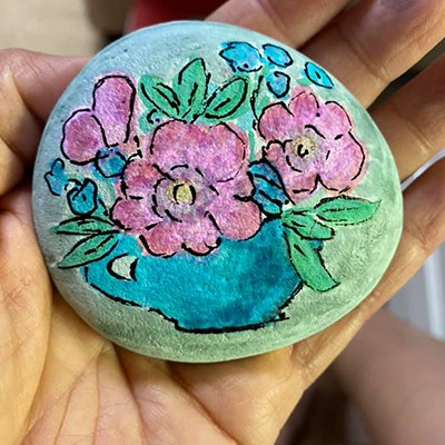 flower painted on rock with brush markers