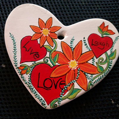 heart shape live love laugh painted on heart rock