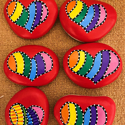 bright red colorful heart shapes painted with acrylic paint pens on rock